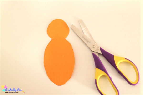 step 1 of making a Thanksgiving turkey craft with buttons. Cut the orange card stock to form turkey's body