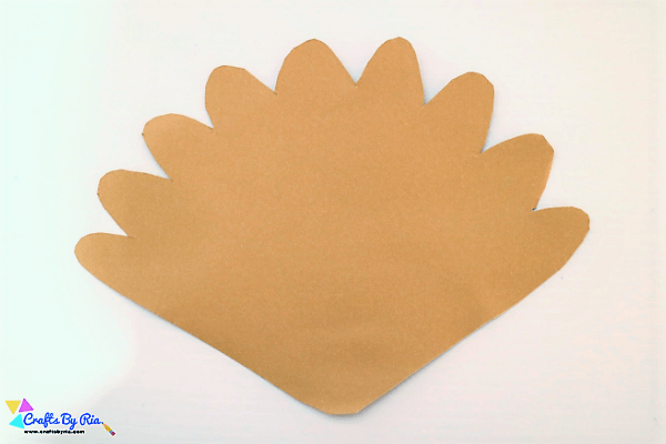Step 4 of Thanksgiving turkey craft with buttons- draw a feather shape on card stock paper