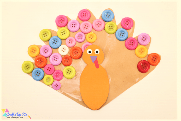 step 6 of Thanksgiving turkey craft with buttons- stick the buttons and turkey's body on the feather