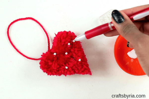 how to make a pom pom heart with beads -glue the beads on the pom pom heart