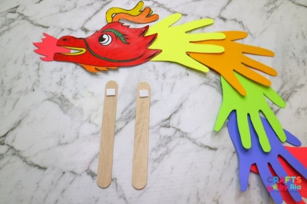 To make the handprint paper dragon puppet, stick two popsicle sticks behind it