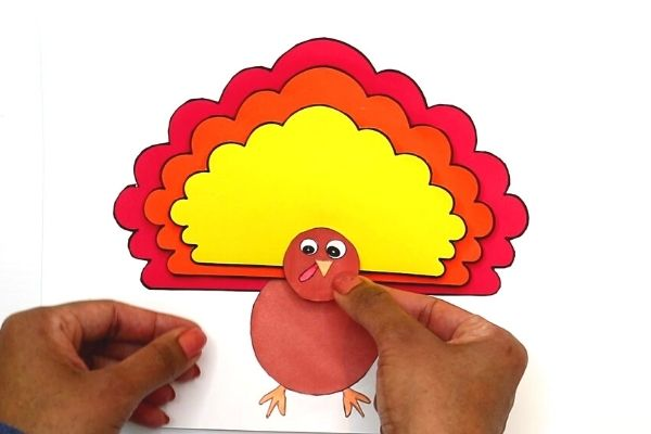 Stick the paper turkey craft's head on top of the feather