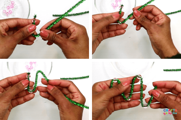 Make several U shapes to form the shape of a Christmas tree and thread beads through them.