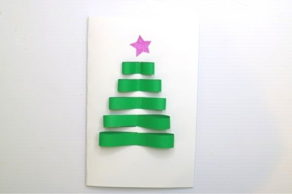 Stick the small bow-like shapes to the fron of the card.